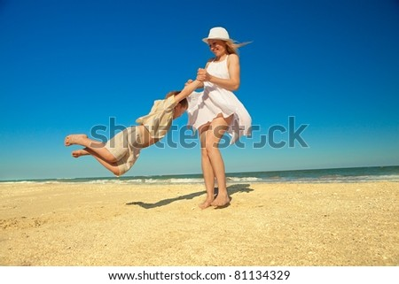 Mother twirling her son on  beach while on vacation - stock photo
