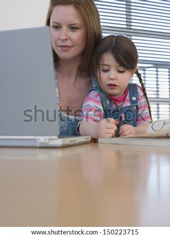 Mother using laptop while daughter coloring at table in house - stock photo