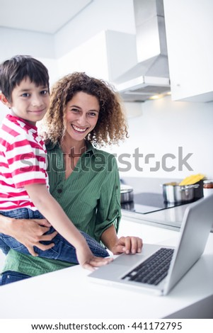 Mother using laptop with son in kitchen at home - stock photo