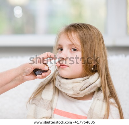 Mother using nose spray to cure her teen girl