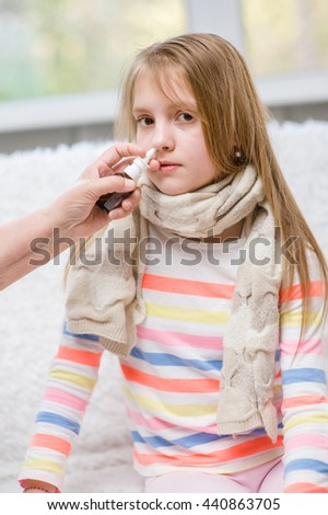 Mother using nose spray to cure her teen girl - stock photo