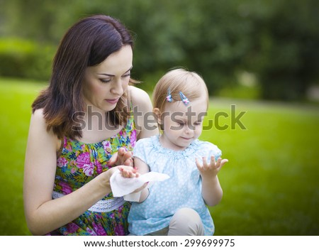Mother using wet wipes for her daughter on white park background - stock photo