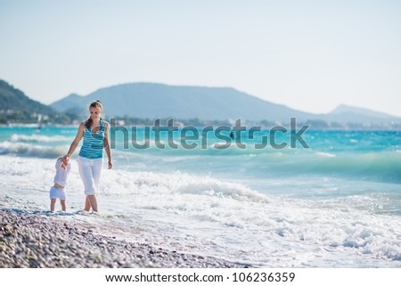 Mother walking with baby on seashore