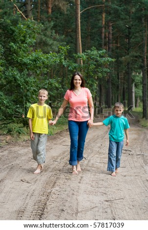 Mother walking with her children in the forest - stock photo