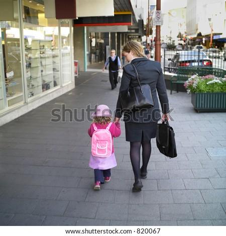 Mother walks her daughter to school, holding hands - stock photo