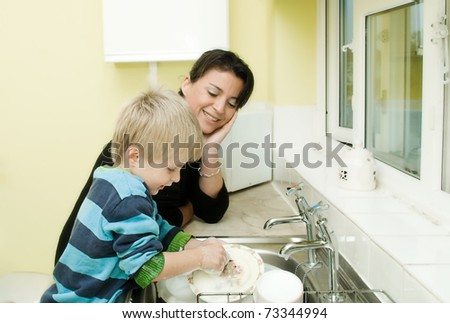 Mother watching child do the dishes in the family kitchen - stock photo