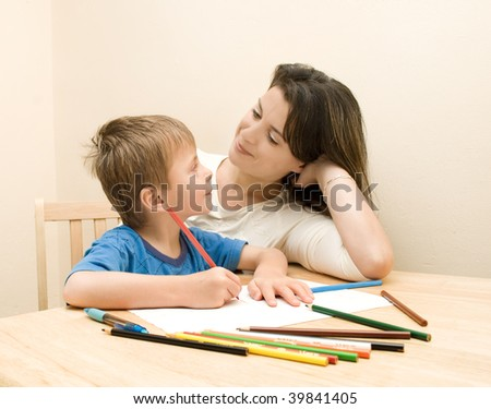 Mother watching child draw. - stock photo