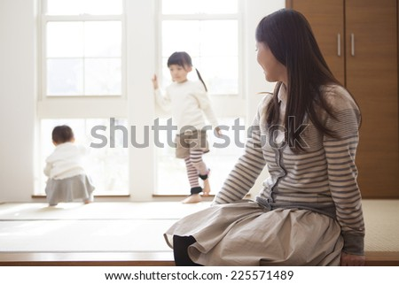 Mother watching children playing - stock photo