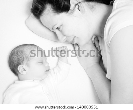 mother watching her cute baby sleeping in bed, black and white image - stock photo