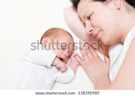 mother watching her month old son sleeping in bed - stock photo