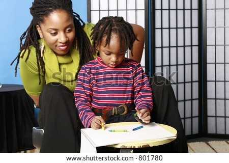 Mother watching her son draw - stock photo
