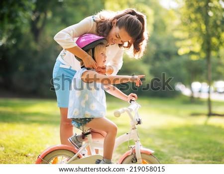 Mother wearing helmet on baby girl on bicycle - stock photo