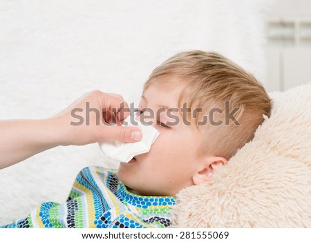 mother wipes her nose son - stock photo