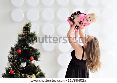 Mother with a baby in her arms. Little girl laughs. Mother in brown dress. Woman lifts up the baby. In the background the Christmas decorations. - stock photo