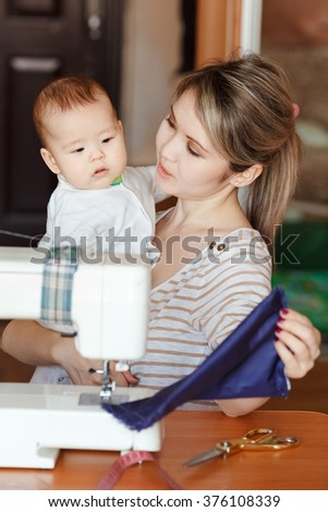 Mother with a baby shows her work, sewing at home. Raising children, parents and children, child care, nanny.