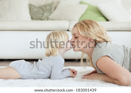 Mother with a child playing together at home - stock photo