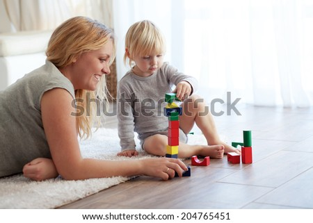 Mother with a child playing with wooden blocks at home - stock photo