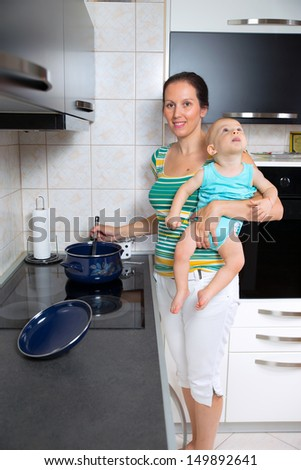 mother with a newborn baby cook food in the kitchen - stock photo