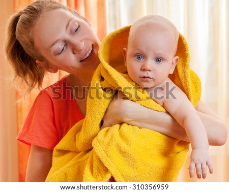 Mother with adorable pretty baby, kid covered with bath towel. After shower. Happy family portrait. - stock photo