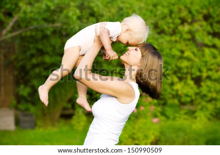 Mother with baby at outdoor. Happy family. - stock photo