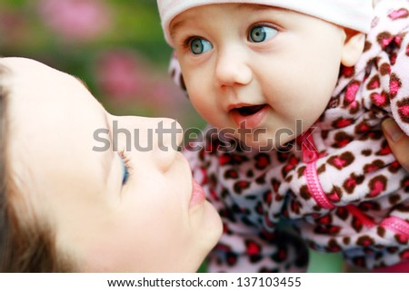 Mother with baby at outdoors in spring blooming garden - stock photo