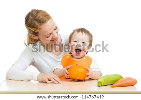 Mother with baby at the table. Boy holding pumpkin - stock photo