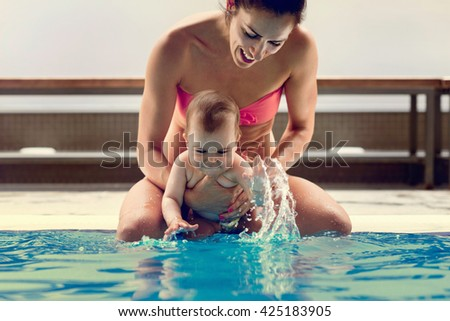 Mother with baby boy sitting on the swimming pool edge, baby splashing. - stock photo