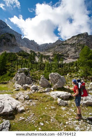 mother with baby carrier carrying a son in alps on a sunny day
