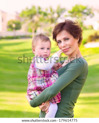 Mother with baby daughter having fun outdoor, relaxation on backyard, walking in the park, enjoying warm spring weather   - stock photo
