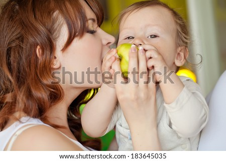 Mother with baby eating apple - stock photo