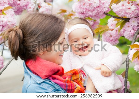 Mother with baby in spring garden - stock photo
