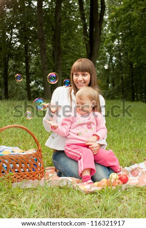 Mother with baby in the park looking at soap bubbles