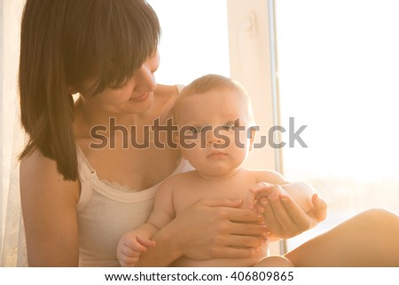 Mother with baby in white room at home near window - stock photo