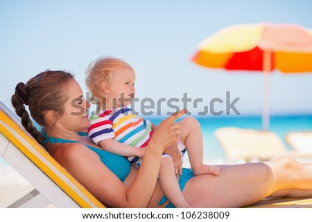 Mother with baby laying on sunbed and pointing on copy space - stock photo