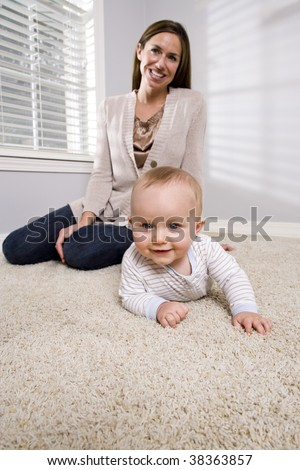 Mother with baby learning to crawl - stock photo