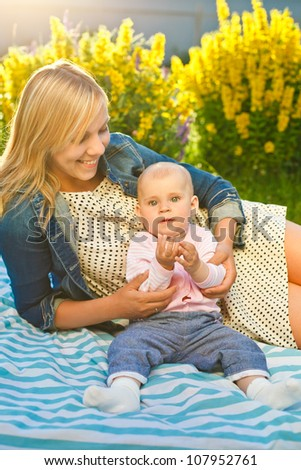 mother with baby lying outdoors in sunny day and teaching clap one�s hands - stock photo