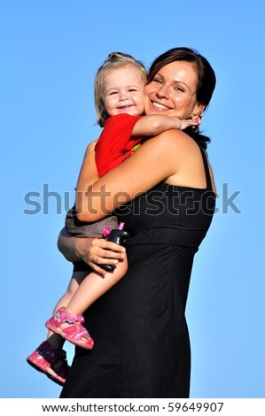 Mother with baby on blue sky background - stock photo