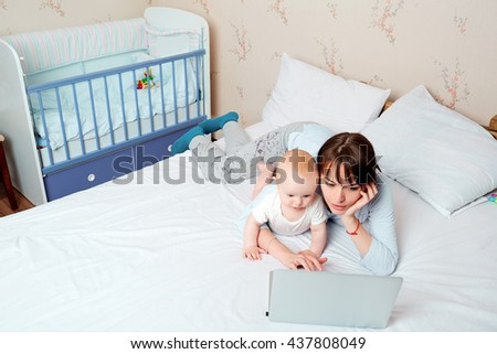 Mother with baby on the bed looking at a laptop with enthusiasm in the children's room.Top view. - stock photo