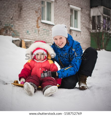 Mother with baby on the sled in the winter. - stock photo