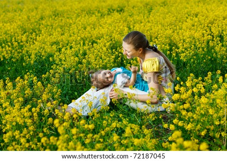 mother with baby on yellow field
