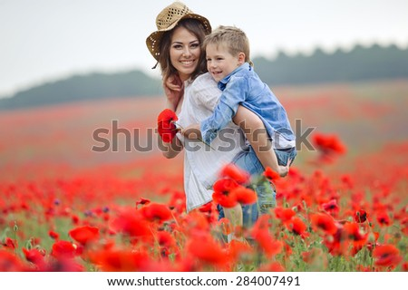 Mother with baby playing in a field of poppies - stock photo