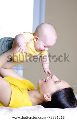Mother with baby playing on bed - stock photo