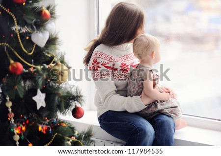 Mother with baby sitting by the window. Christmas decorations. On Christmas, waiting for a miracle. A woman with a child looking out the window. - stock photo