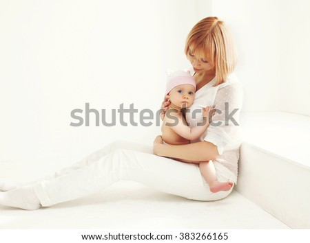 Mother with baby sitting home in white room near window - stock photo