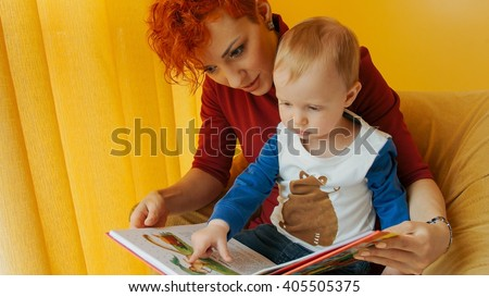 Mother with baby sitting in chair and reading story with pictures. Little boy looks into book and shows finger in book. Family, early development, activity, learning. Cute kid, child play with mom. - stock photo