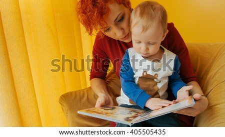 Mother with baby sitting in chair and reading story with pictures. Little boy looks into book and shows finger in book. Family, early development, activity, learning. Cute kid, child play with mom.