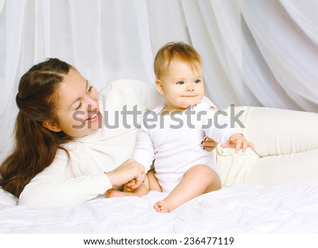 Mother with baby sitting together on the bed