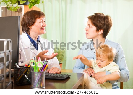 mother with baby talking with friendly  doctor at clinic office