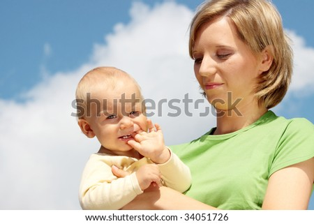 Mother with baby under blue clear sky
