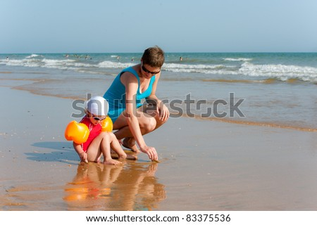 Mother with child are looking for shells